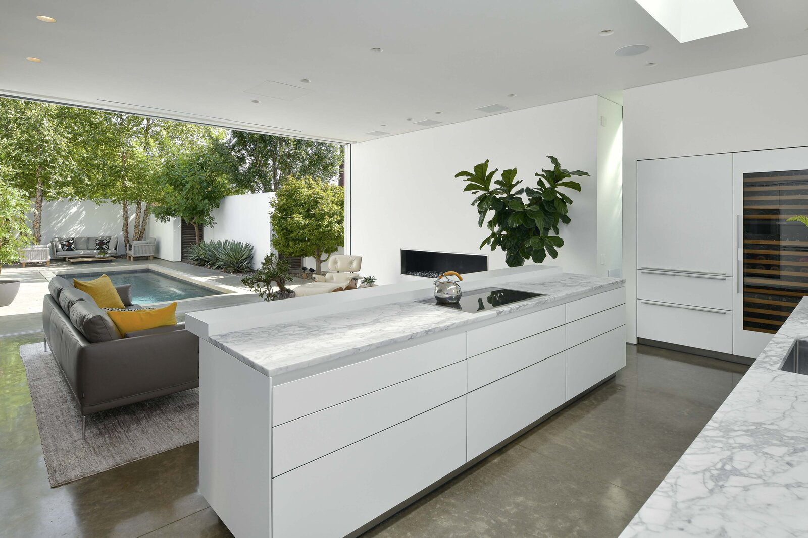 """Kitchen The Bulthaup kitchen features sleek cabinetry, marble countertops, and high-end appliances from <span style=""""font-family: Theinhardt, -apple-system, BlinkMacSystemFont, &quot;Segoe UI&quot;, Roboto, Oxygen-Sans, Ubuntu, Cantarell, &quot;Helvetica Neue&quot;, sans-serif;"""">Gaggenau and Sub-Zero. A central island overlooks the living room and courtyard, while a large skylight illuminates the space from above.</span>  Photo 4 of 11 in A Chic Urban Retreat by Modernist Architect Lionel Morrison Asks $2.5M in Dallas"""