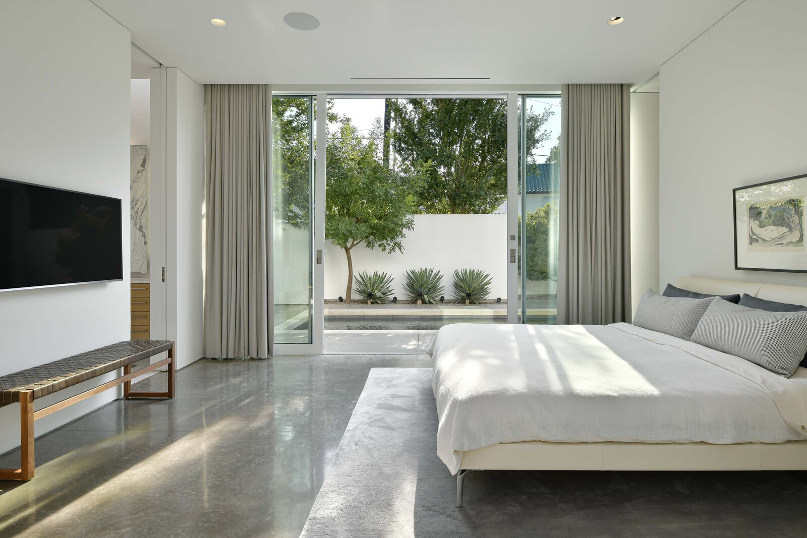 Bedroom, Bed, Ceiling Lighting, Concrete Floor, and Bench Another set of sliding glass doors provide access to the courtyard. Pocket doors open to the en suite bathroom at both ends of the room.  Photo 7 of 11 in A Chic Urban Retreat by Modernist Architect Lionel Morrison Asks $2.5M in Dallas