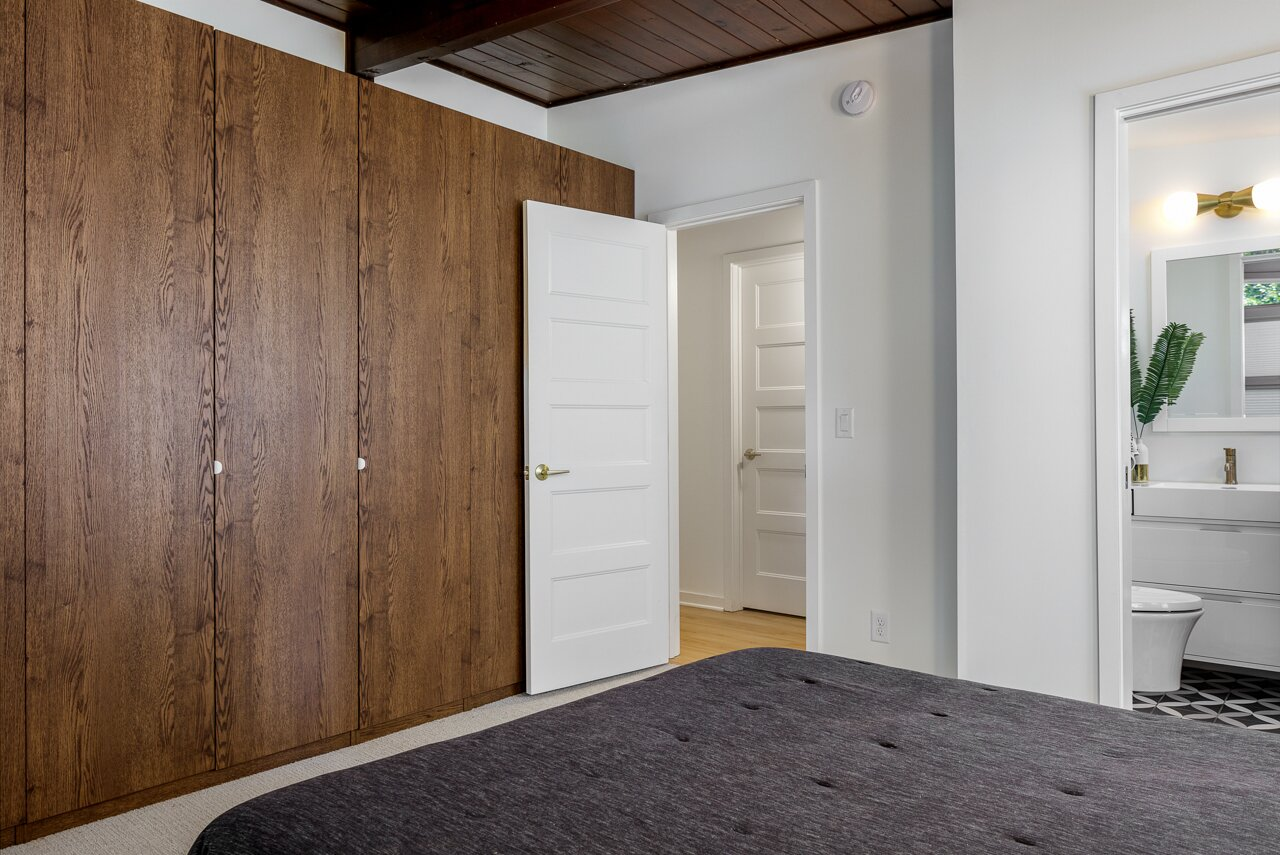 A fresh wall of cabinetry replaces the previous built-in closets, while a new bathroom was added along one side.  Photo 16 of 21 in Before & After: A Renovated Iowan Midcentury House Impresses With an Affordable $330K Price Point