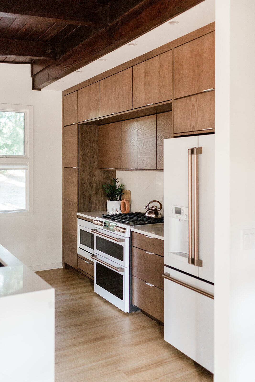 The updated kitchen features all-new cabinetry and appliances from GE's Cafe line.  Photo 12 of 21 in Before & After: A Renovated Iowan Midcentury House Impresses With an Affordable $330K Price Point