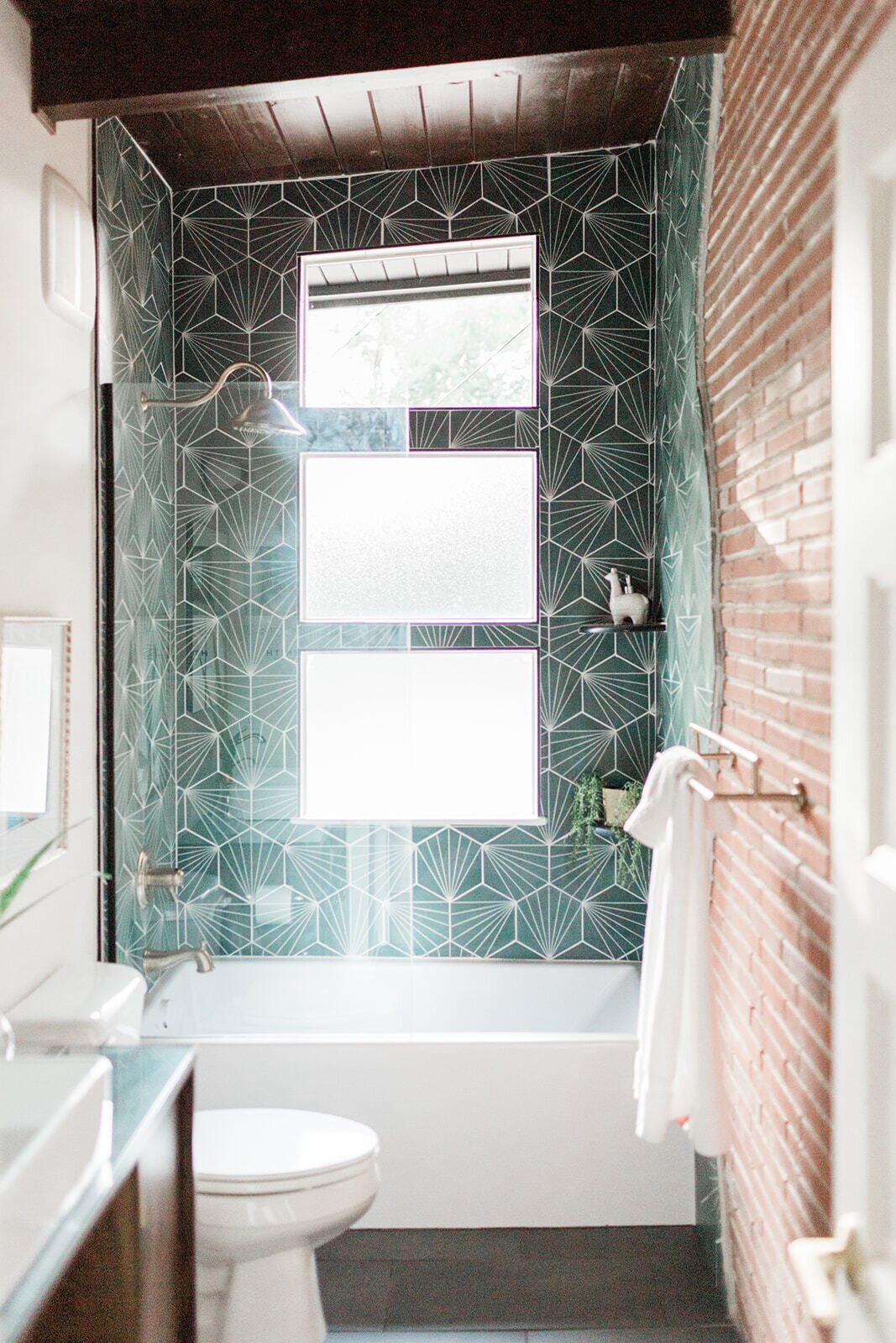 Basking in natural light, the renovated bathroom bathroom offers all-new finishes, including brightly colored tiles that contrast with the refinished brick wall.  Photo 19 of 21 in Before & After: A Renovated Iowan Midcentury House Impresses With an Affordable $330K Price Point