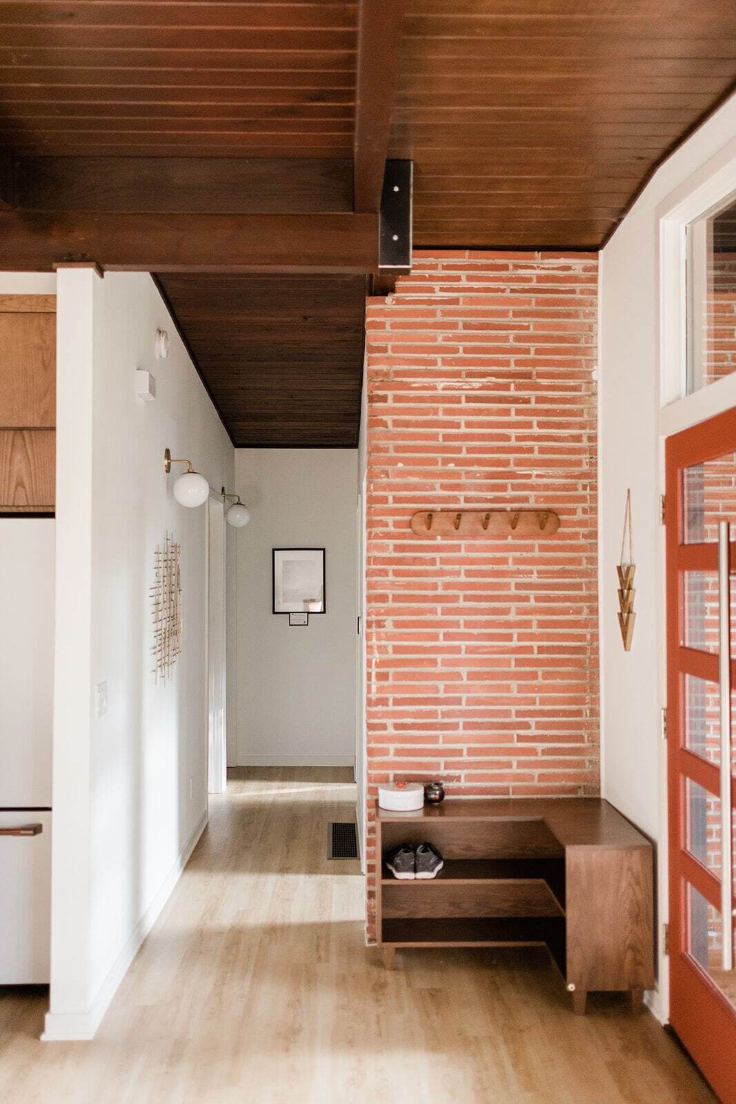 With the closet removed, a brick wall was exposed to visually connect the interior and exterior. A new glass front door illuminates the entryway with natural light.  Photo 5 of 21 in Before & After: A Renovated Iowan Midcentury House Impresses With an Affordable $330K Price Point
