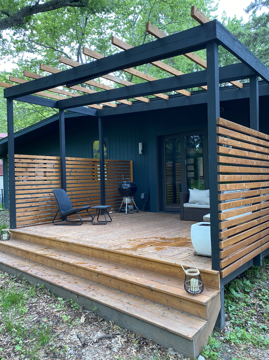 Perfect for a cozy movie night, the partially-enclosed back deck comes with a built-in projector and screen that folds down near the steps.  Photo 21 of 21 in Before & After: A Renovated Iowan Midcentury House Impresses With an Affordable $330K Price Point