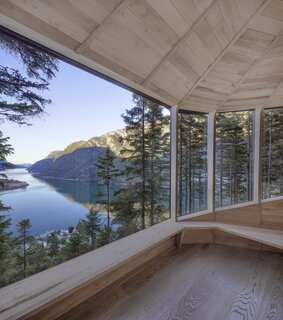 Inside, wraparound windows provide panoramic views of the fjord and mountains.