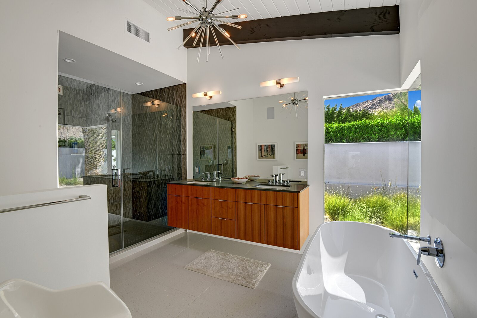 The master bathroom also overlooks the private patio and comes with a floating vanity, large shower, and free-standing soaking tub.  Photo 13 of 17 in A Palm Springs Alexander Home Sings After a Chic Renovation and Hits the Market to the Tune of $2.1M