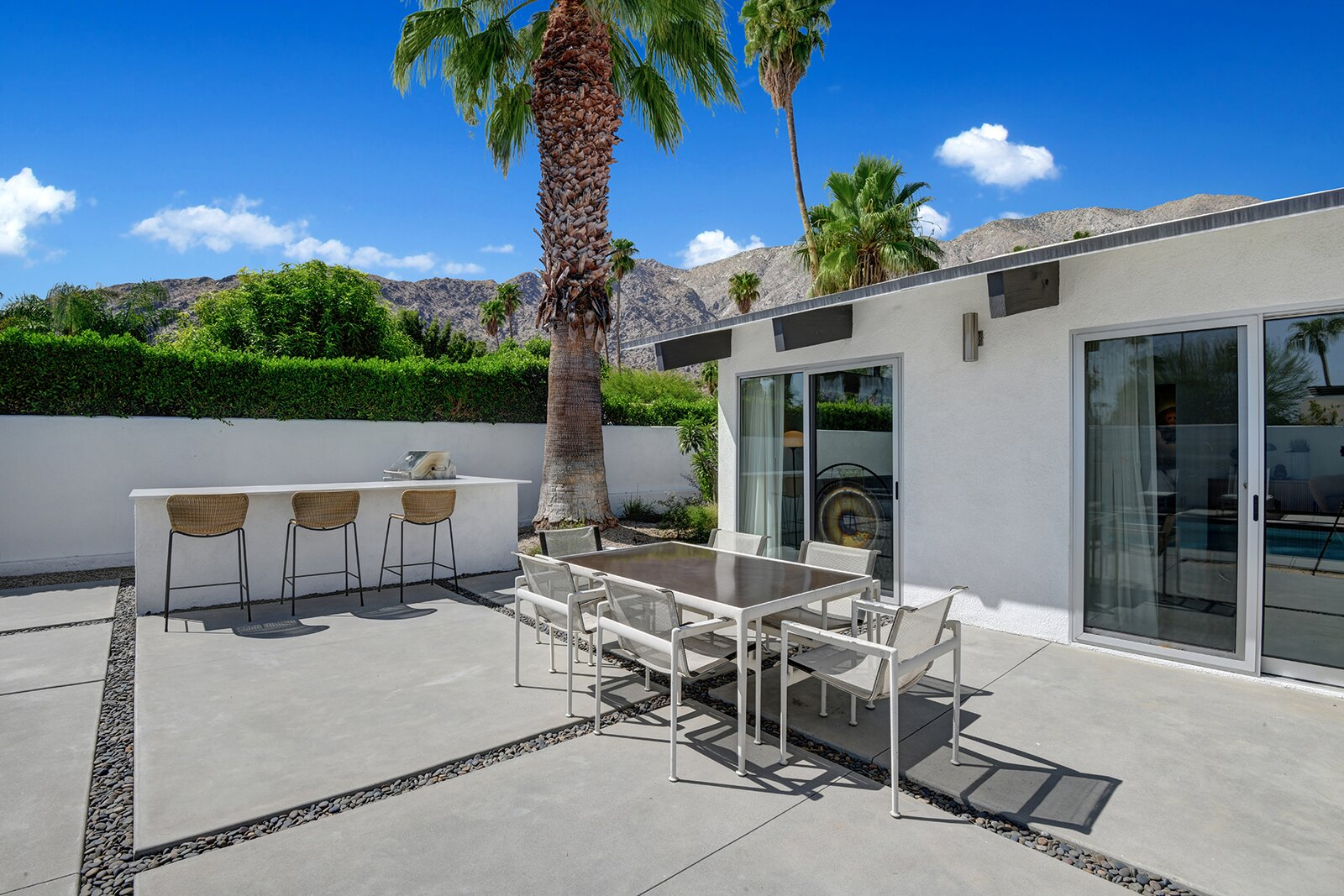 The patio also offers a built-in grill and bar, as well as numerous areas for lounging and entertaining. Nearly two-thirds of the .23-acre lot is enclosed to provide greater privacy.  Photo 10 of 17 in A Palm Springs Alexander Home Sings After a Chic Renovation and Hits the Market to the Tune of $2.1M