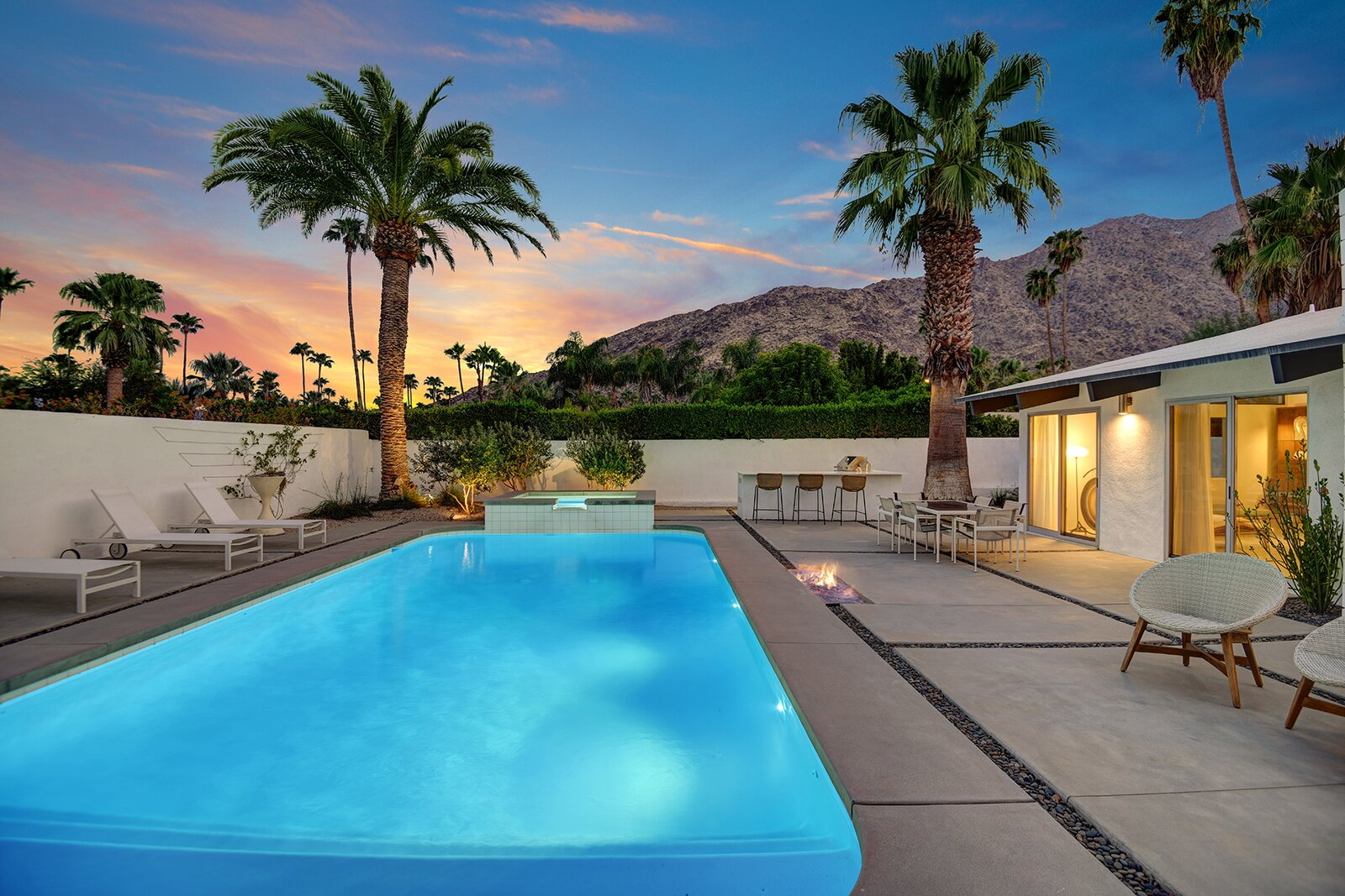 Once the sun goes down, the backyard pool glistens alongside an adjacent fire pit and spa.  Photo 16 of 17 in A Palm Springs Alexander Home Sings After a Chic Renovation and Hits the Market to the Tune of $2.1M
