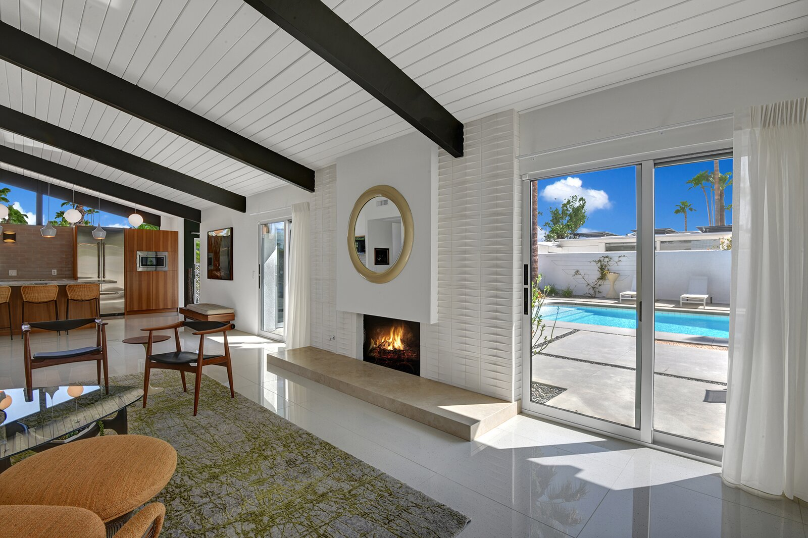 Another view of the living area shows the full-height fireplace, which the current owners faced with new tile.  Photo 4 of 17 in A Palm Springs Alexander Home Sings After a Chic Renovation and Hits the Market to the Tune of $2.1M