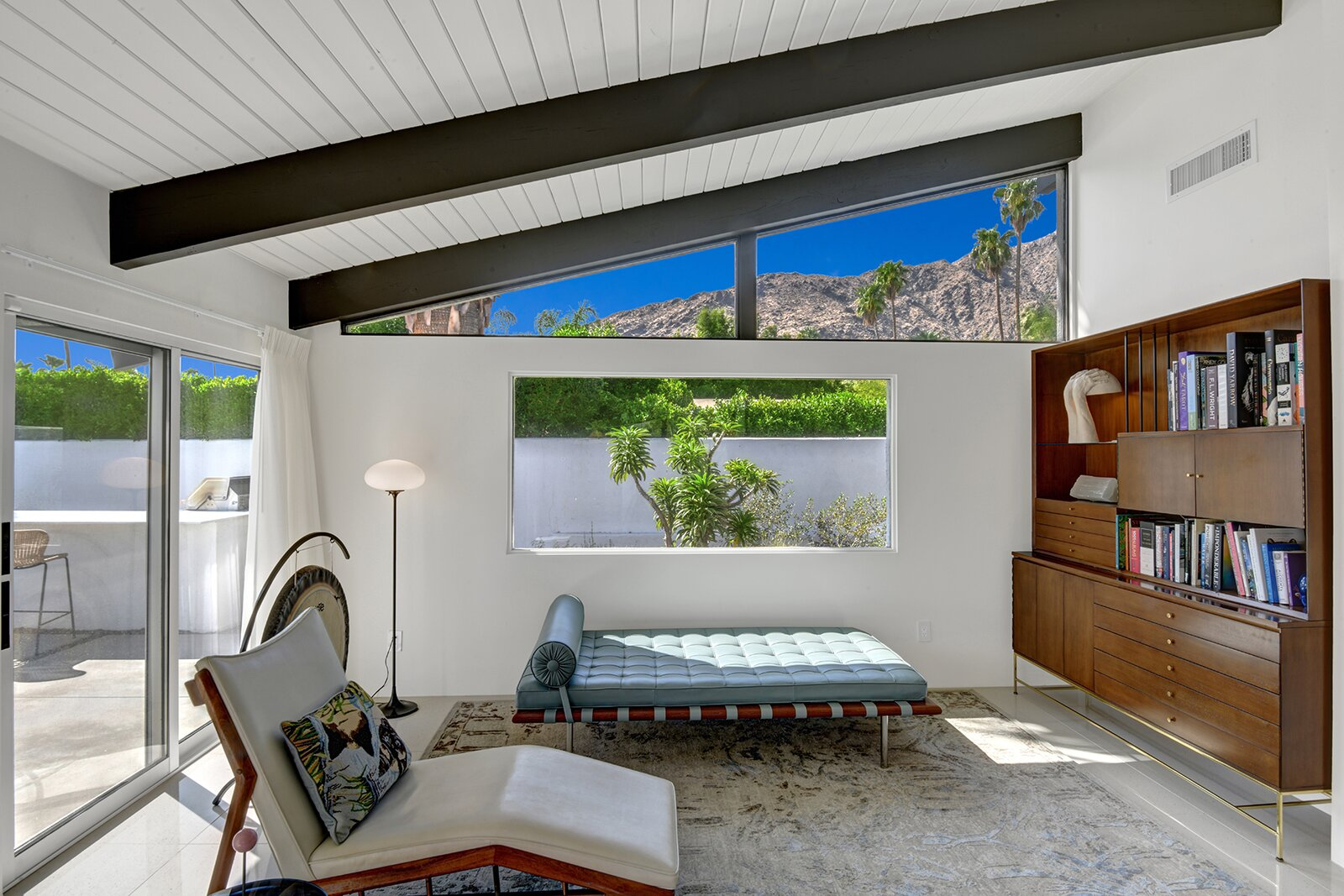 At one end of the living area, windows run along the roofline, framing views of the surrounding mountaintop. The purchase price includes most of the home's furnishings except for the current owner's collection of artwork and other personal belongings.  Photo 3 of 17 in A Palm Springs Alexander Home Sings After a Chic Renovation and Hits the Market to the Tune of $2.1M