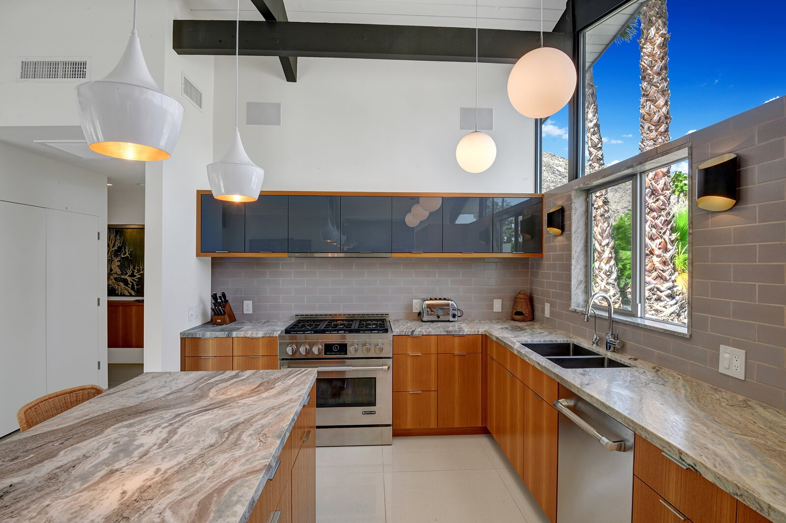 Thomboy Properties completely renovated the space in 2019, adding new cabinetry and appliances, while the current owners incorporated marble counters and new backsplash tile.  Photo 6 of 17 in A Palm Springs Alexander Home Sings After a Chic Renovation and Hits the Market to the Tune of $2.1M