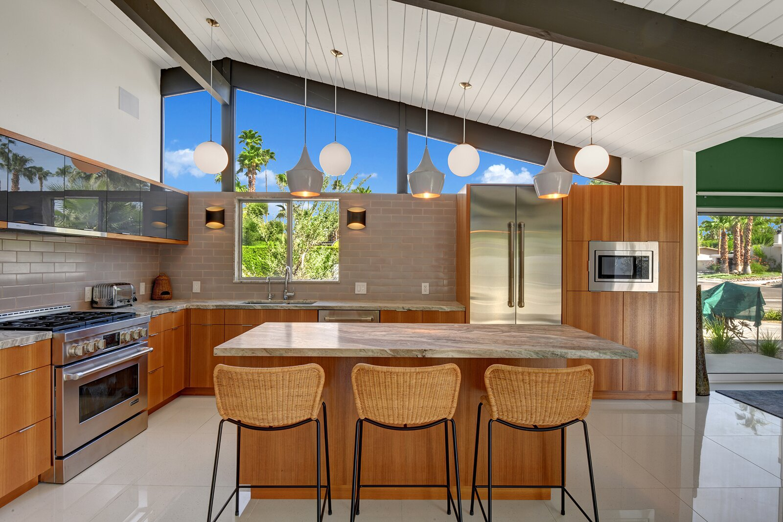 At the opposite end of the space, a large kitchen opens to the living area.  Photo 5 of 17 in A Palm Springs Alexander Home Sings After a Chic Renovation and Hits the Market to the Tune of $2.1M