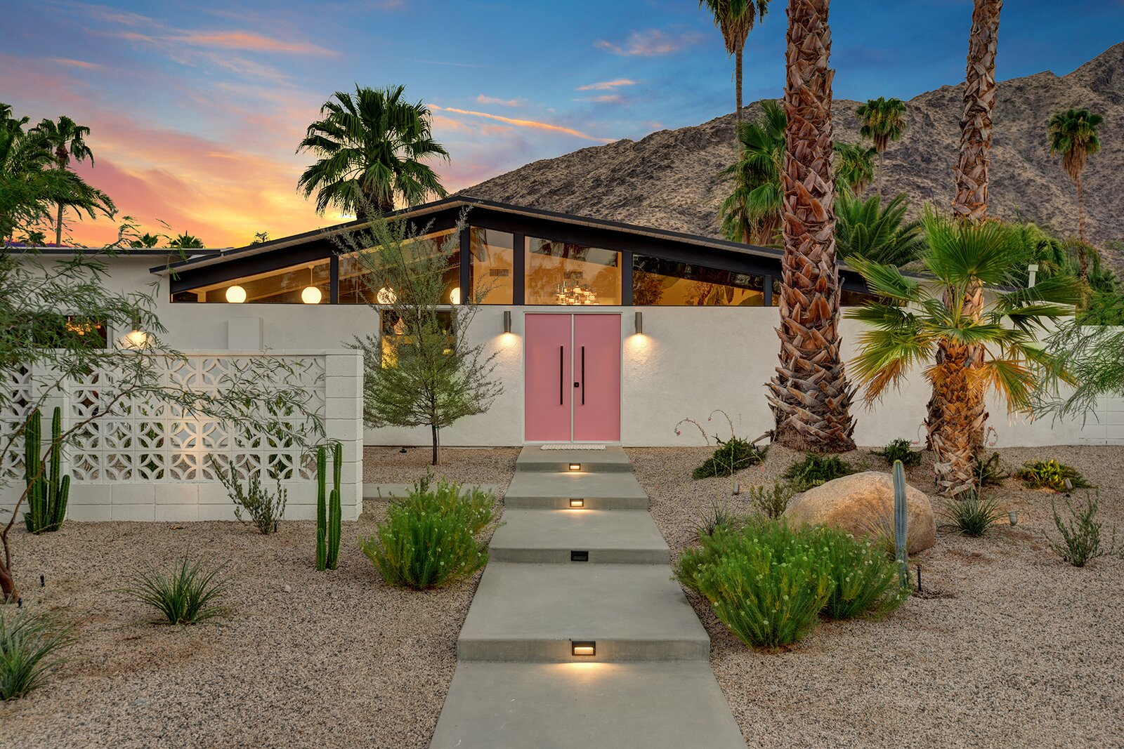 Complete with a decorative block wall and pink front door, the home's front facade looks picture-perfect against a backdrop of the desert landscape.  Photo 17 of 17 in A Palm Springs Alexander Home Sings After a Chic Renovation and Hits the Market to the Tune of $2.1M