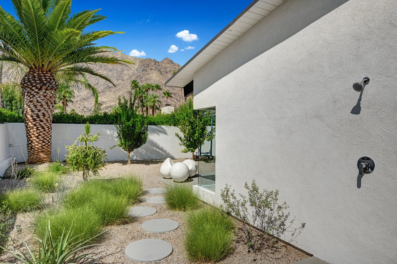 An outdoor shower is located around from the pool.  Photo 11 of 17 in A Palm Springs Alexander Home Sings After a Chic Renovation and Hits the Market to the Tune of $2.1M