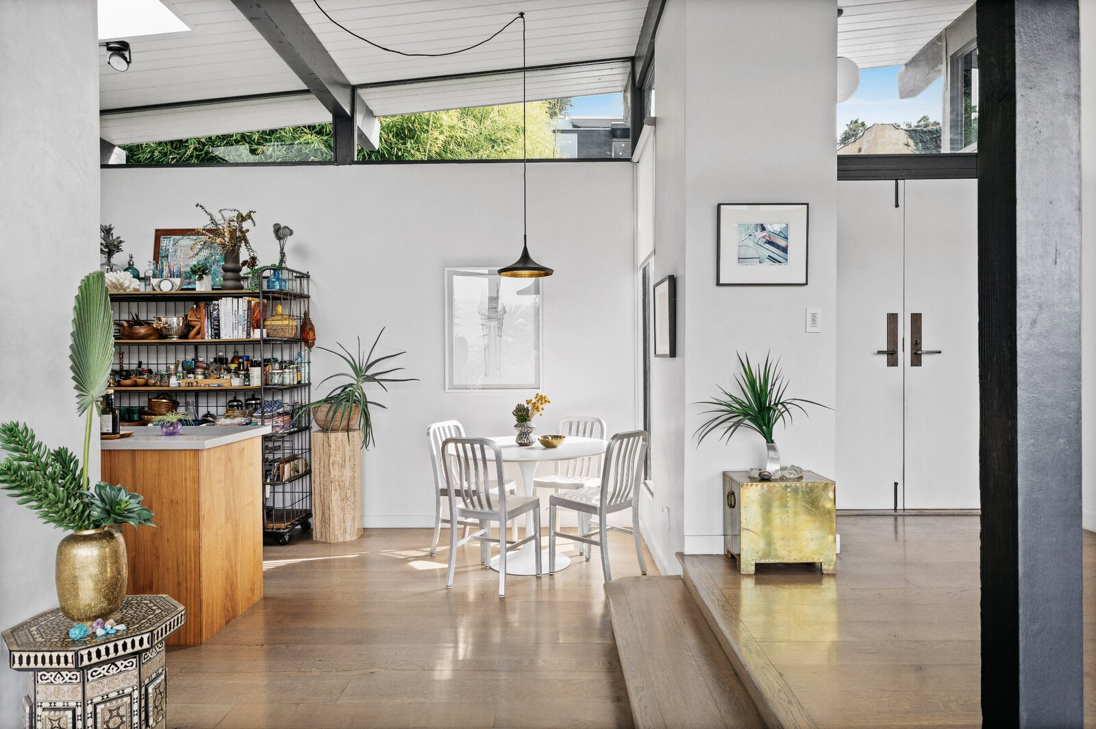 A dining nook is located next to the kitchen. Steps lead up to the entryway, which connects to a hallway leading to the home's three bedrooms.  Photo 6 of 16 in Raised on Stilts, a $2.5M Midcentury in Los Angeles Captures Beguiling Views