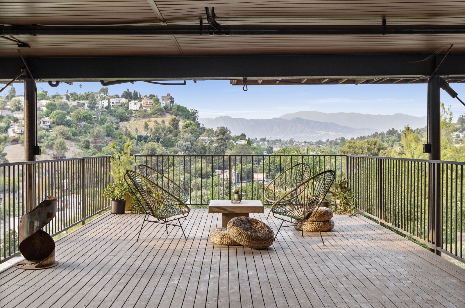 Views from the shaded deck look out on the surrounding hills.  Photo 11 of 16 in Raised on Stilts, a $2.5M Midcentury in Los Angeles Captures Beguiling Views