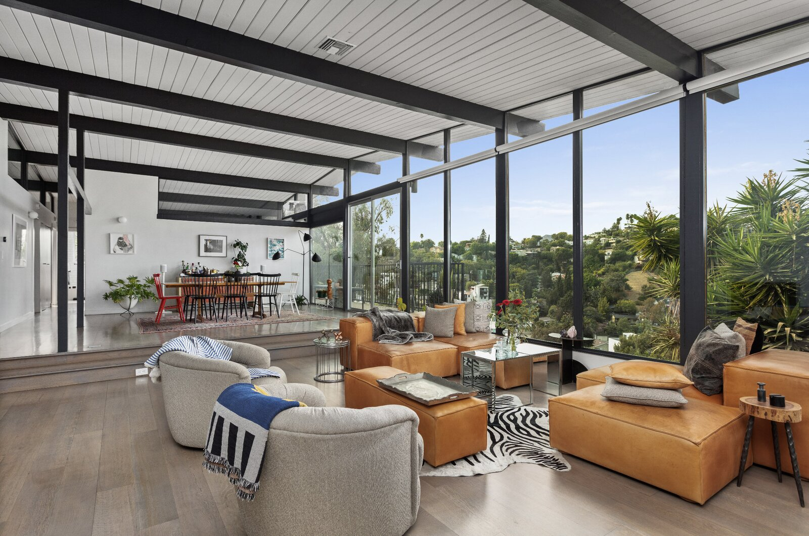Separated by two steps, the raised dining area was once closed off from the living room by a wall and doorway. The team at Tradecraft opened up the space and opted for a contrasting color scheme to emphasize the home's post-and-beam construction.  Photo 3 of 16 in Raised on Stilts, a $2.5M Midcentury in Los Angeles Captures Beguiling Views