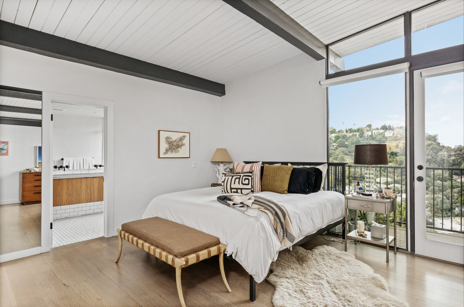 The first stop along the hallway is the principal suite, which also features direct access to the balcony along the dining area.  Photo 7 of 16 in Raised on Stilts, a $2.5M Midcentury in Los Angeles Captures Beguiling Views