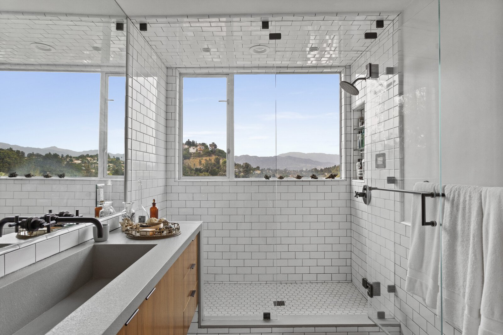 The en suite bathroom features a large shower with framed views of the Franklin Hills and San Gabriel Mountains.  Photo 8 of 16 in Raised on Stilts, a $2.5M Midcentury in Los Angeles Captures Beguiling Views