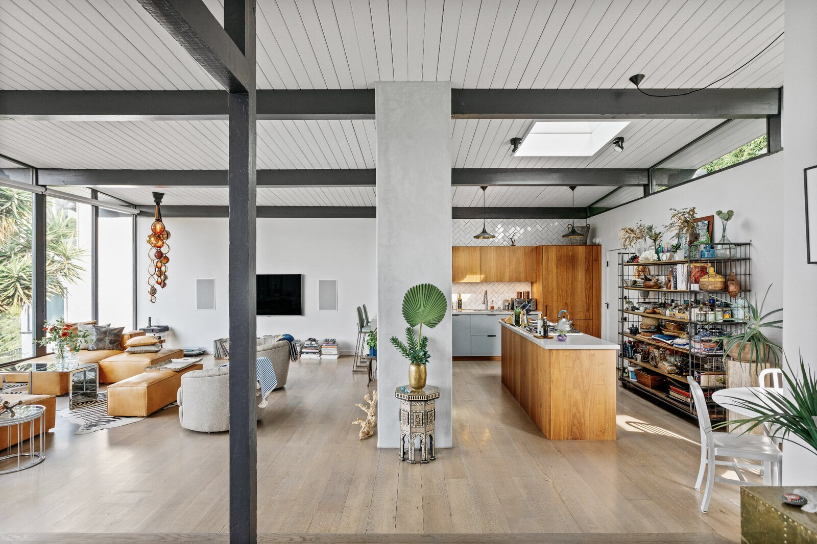 Viewed from the dining area, the kitchen features a central island and wood cabinets.  Photo 5 of 16 in Raised on Stilts, a $2.5M Midcentury in Los Angeles Captures Beguiling Views