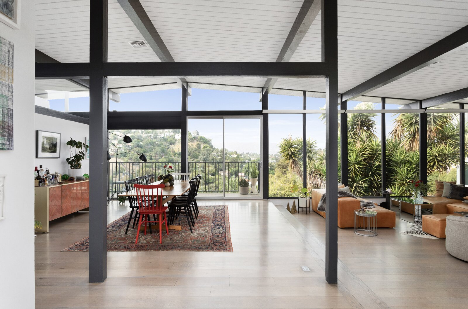 Inside, a two-level living and dining area features floor-to-ceiling windows that welcome in abundant sunlight.  Photo 2 of 16 in Raised on Stilts, a $2.5M Midcentury in Los Angeles Captures Beguiling Views