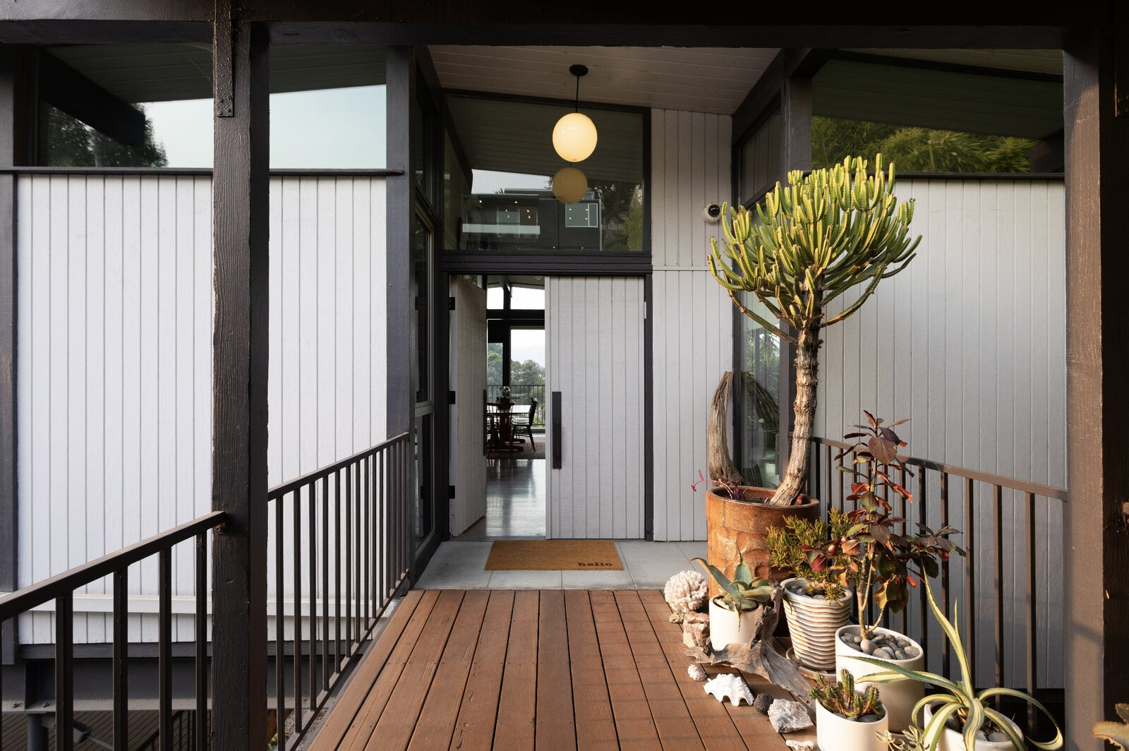 Above the patio, an exterior walkway connects the main entrance with the carport.  Photo 14 of 16 in Raised on Stilts, a $2.5M Midcentury in Los Angeles Captures Beguiling Views
