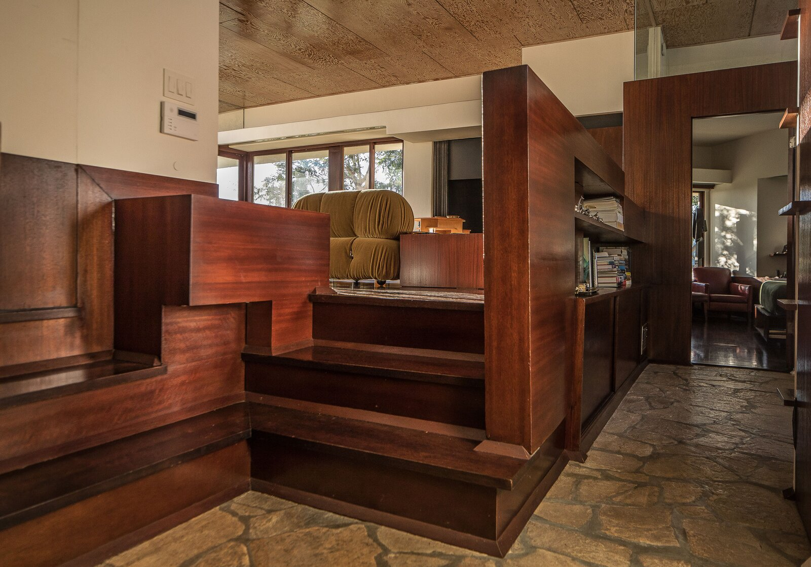 At the opposite end of the living area, additional built-ins divide public and private spaces, with steps leading down to the unit's entryway and bedrooms.  Photo 6 of 14 in A Newly Restored Schindler Building Lists for $3.65M in L.A.