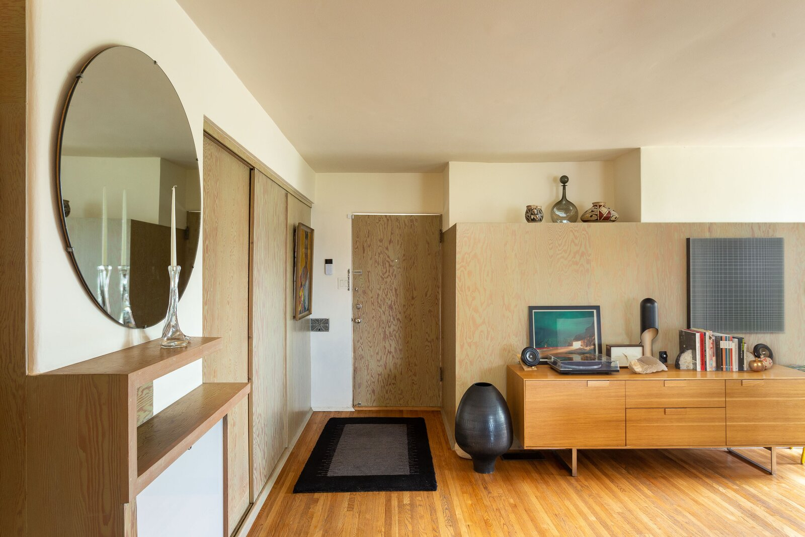 In one of the building's other one-bedroom units, modern additions replicate Schinder's plywood motif with doors and other built-ins.  Photo 10 of 14 in A Newly Restored Schindler Building Lists for $3.65M in L.A.