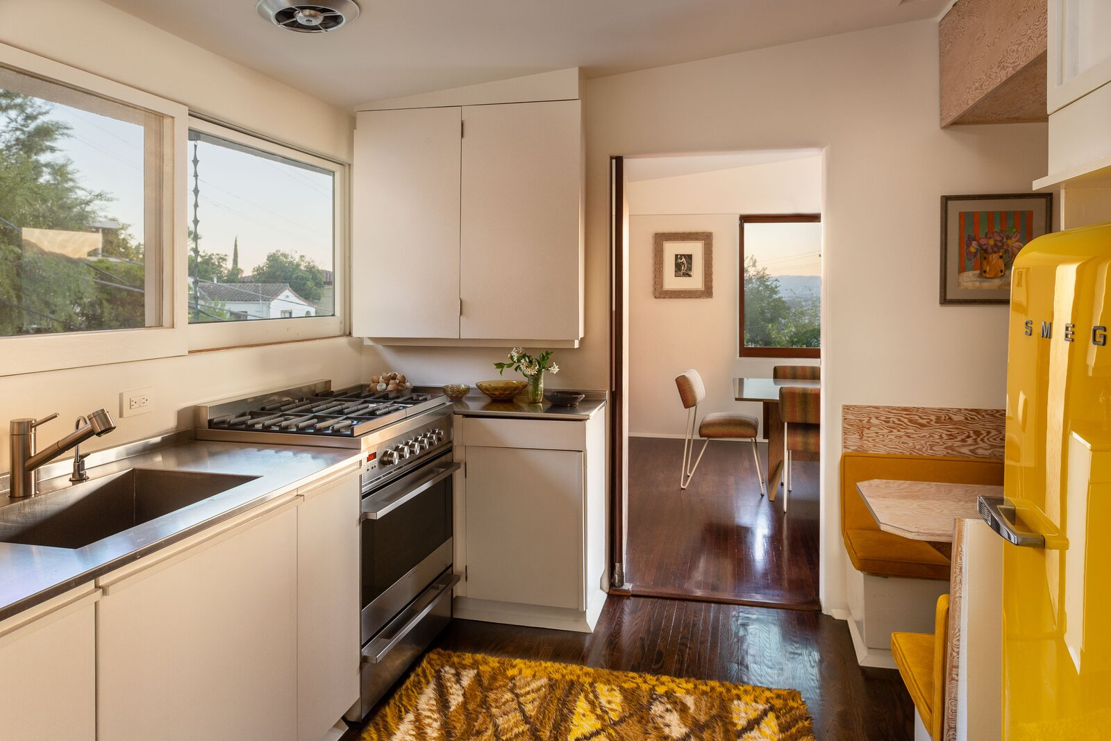 The penthouse's recently remodeled kitchen features updated appliances and finishes, mixed with original features such as a built-in banquette.  Photo 5 of 14 in A Newly Restored Schindler Building Lists for $3.65M in L.A.