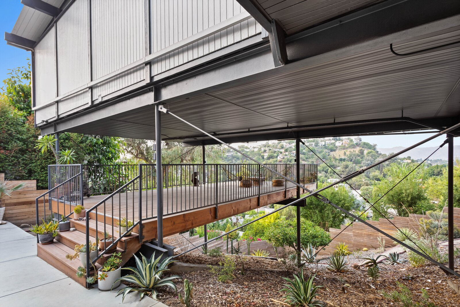 Outside, a large deck runs underneath the home, accessed via a patio along the front.  Photo 10 of 16 in Raised on Stilts, a $2.5M Midcentury in Los Angeles Captures Beguiling Views
