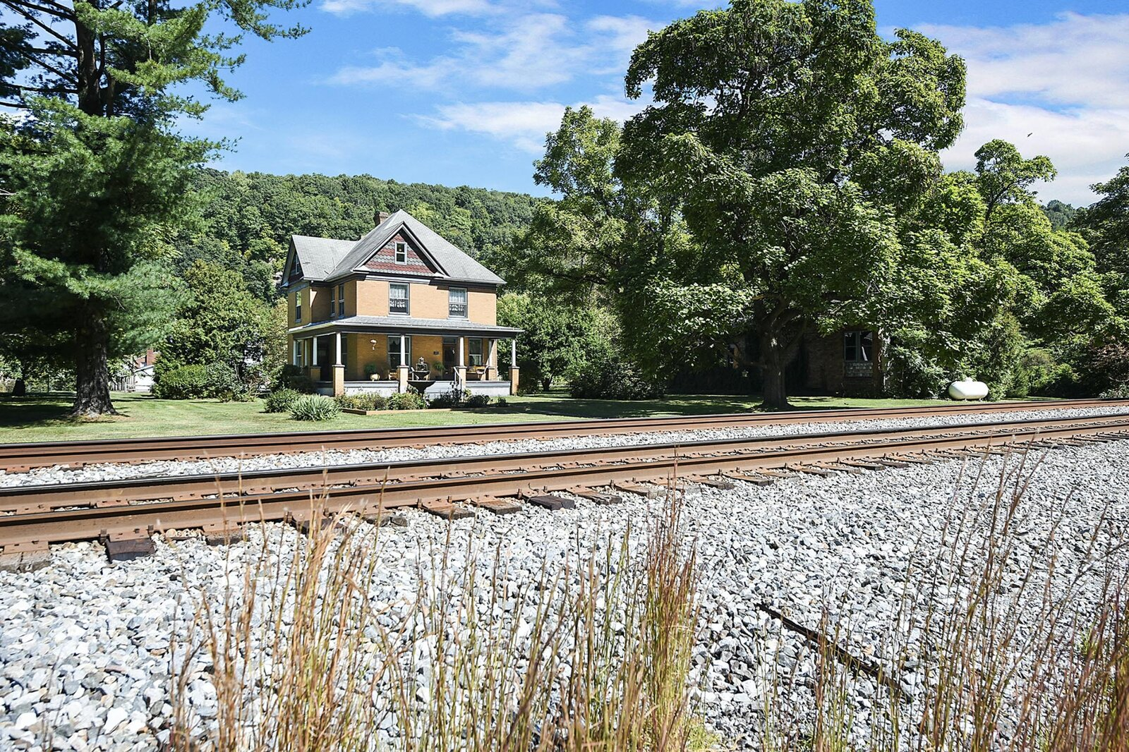 """While the front porch provides the perfect perch to watch passing trains, the agents note that exterior noise from the active railway is not as prominent inside the home.  Photo 23 of 23 in Hey, Horror Movie Buffs—You Can Own the """"Silence of the Lambs"""" House for $299K"""