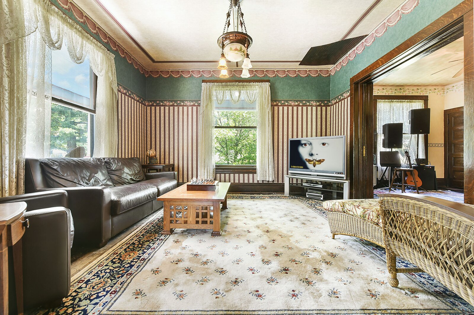 """Another wide doorway with pocket doors separate the music room from the main living area at the front of the home.  Photo 11 of 23 in Hey, Horror Movie Buffs—You Can Own the """"Silence of the Lambs"""" House for $299K"""