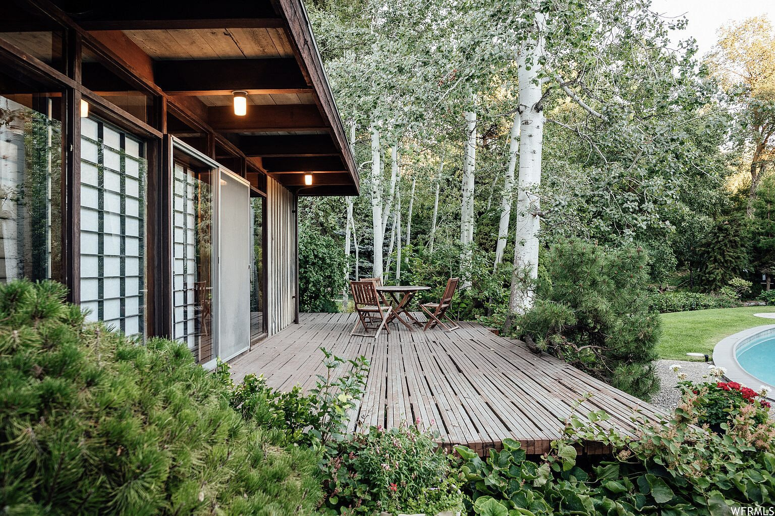 A large deck off of the principal suite provides a space to relax overlooking the pool.  Photo 15 of 18 in This Tranquil, Japanese-Inspired Midcentury Home Asks $1.2M
