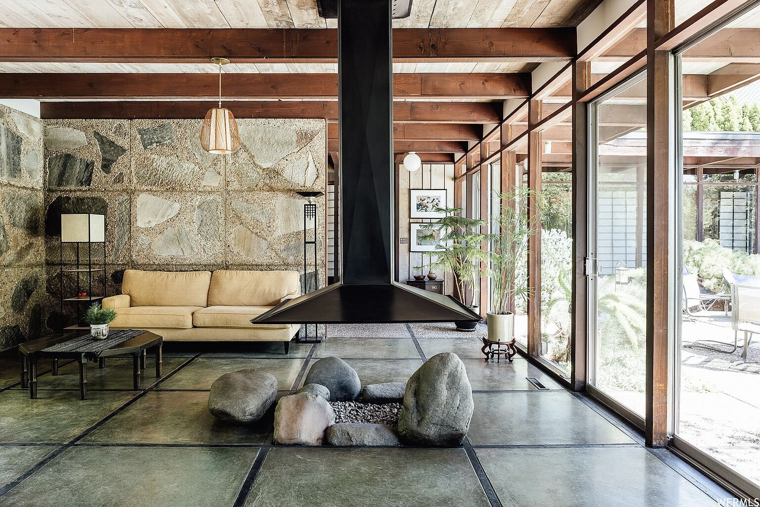 The slabs of concrete and full-height windows continue into the living area, which also features a suspended fireplace hood in the center. In the corner, slabs of concrete embedded with stone carry over from the exterior facade.  Photo 3 of 18 in This Tranquil, Japanese-Inspired Midcentury Home Asks $1.2M