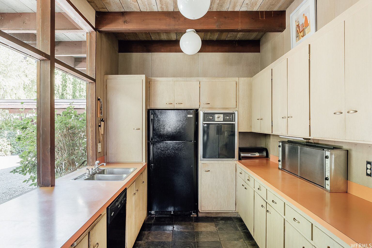 Around the corner from the dining area, the nearly original kitchen features several large windows overlooking the front yard. The space is filled with mix of new and vintage appliances, as well as the original cabinetry and countertops.  Photo 6 of 18 in This Tranquil, Japanese-Inspired Midcentury Home Asks $1.2M