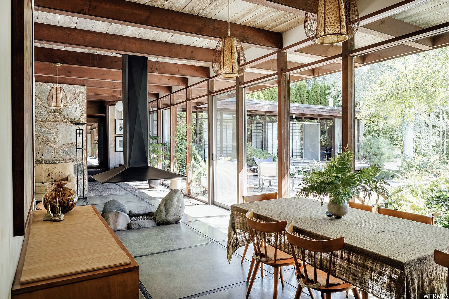 Nearly indistinguishable from the glass window panes, a sliding door behind the fireplace opens the living and dining area to the poolside patio.  Photo 5 of 18 in This Tranquil, Japanese-Inspired Midcentury Home Asks $1.2M