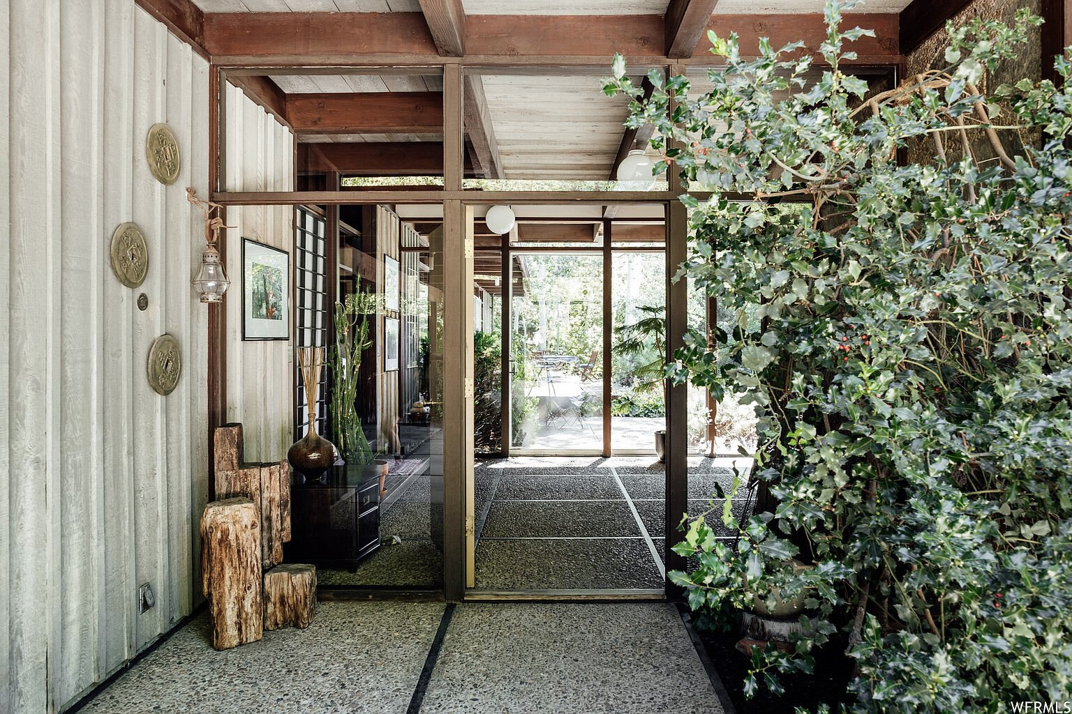 From the gravel driveway, the main entrance opens into a central vestibule, with views of the lush backyard visible through the glass walls straight ahead. Square-shaped slabs of concrete bordered by wood are repeated throughout the interior and exterior.  Photo 2 of 18 in This Tranquil, Japanese-Inspired Midcentury Home Asks $1.2M