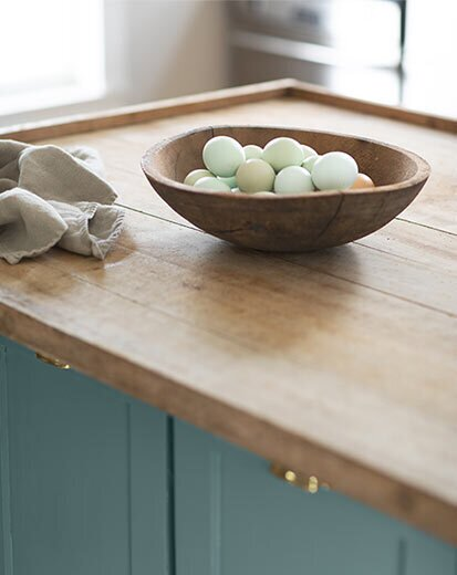 Surrounding the blue-green pick are a range of earthen, warm tones with a lived-in quality.