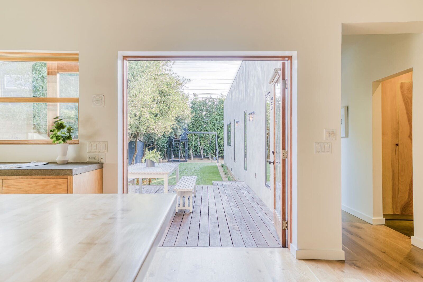 French doors open to the deck and yard, while a long hallway connects the great room to the home's bedrooms.  Photo 6 of 15 in In Los Angeles, a Remixed Craftsman Bungalow Lists for $1.9M