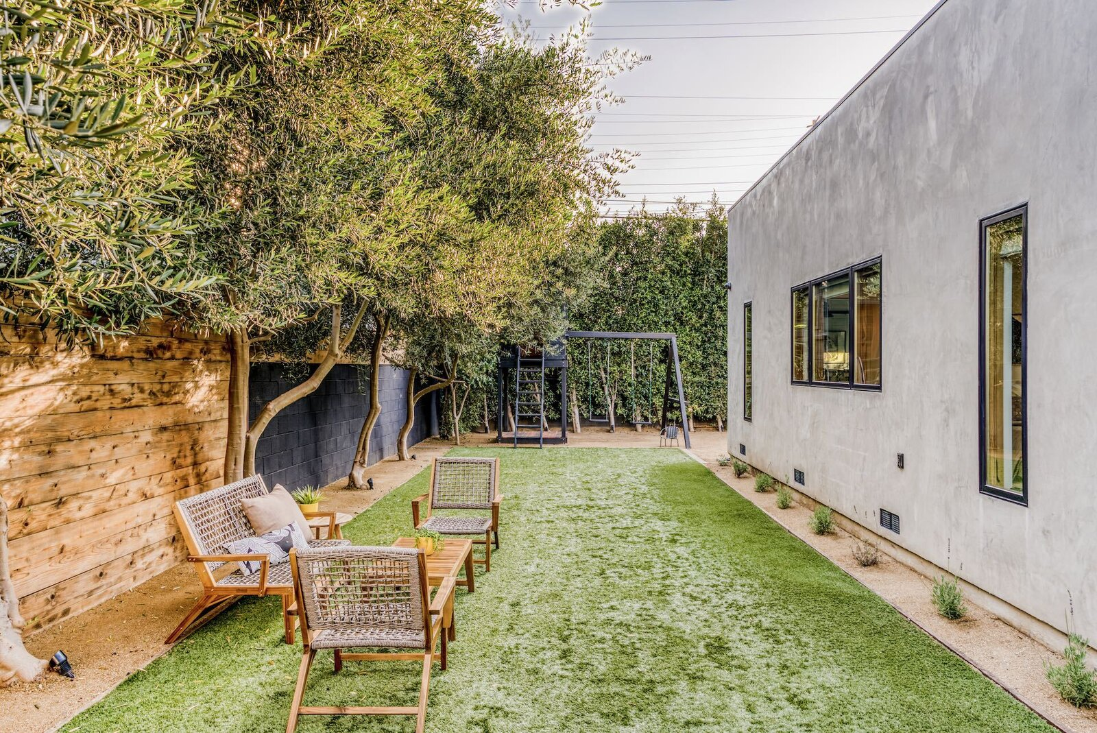 Olive trees line the perimeter of the side yard, which also features space for seating and a swing set in the back corner.  Photo 8 of 15 in In Los Angeles, a Remixed Craftsman Bungalow Lists for $1.9M