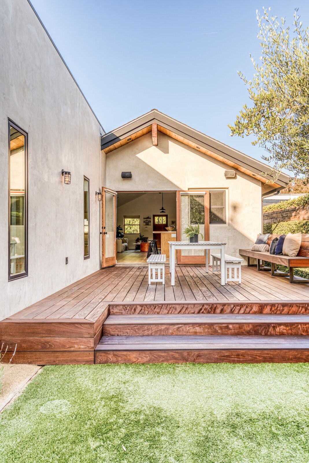 The deck features space for outdoor dining and built-in seating to one side. The original home transitions into a rectangular, modern addition that extends from the rear.  Photo 7 of 15 in In Los Angeles, a Remixed Craftsman Bungalow Lists for $1.9M