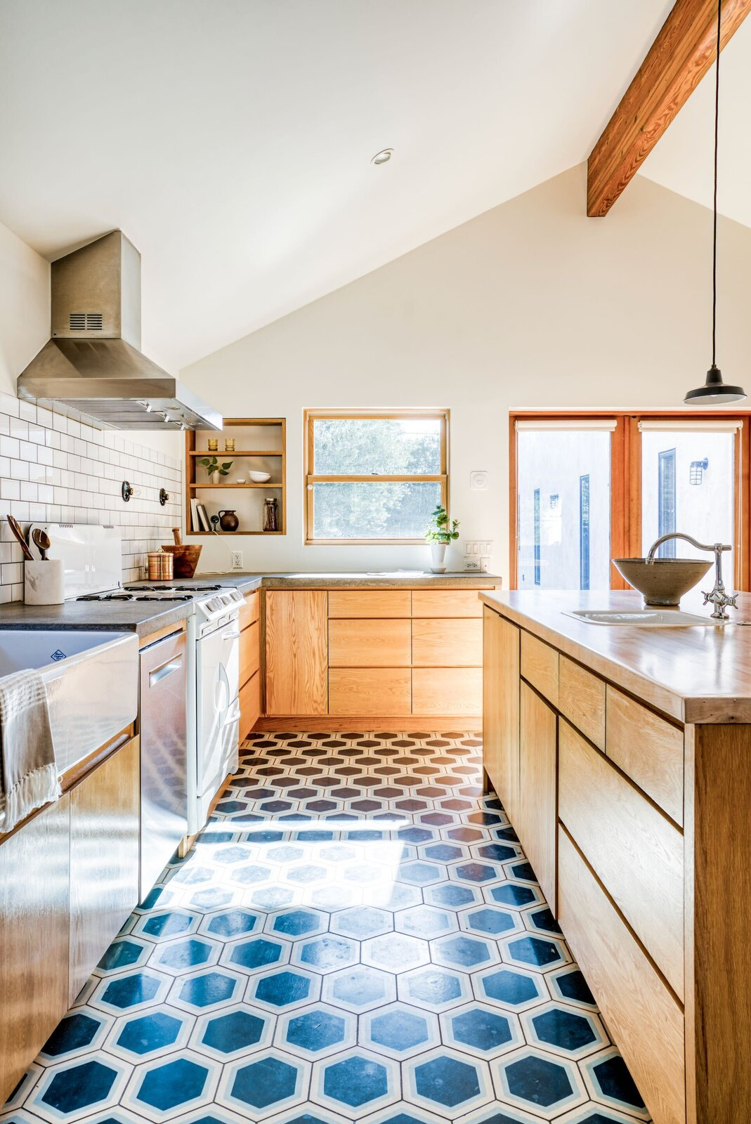 The kitchen features ample wood cabinetry, hexagonal tile flooring in a saturated blue, and a vintage-style range.  Photo 5 of 15 in In Los Angeles, a Remixed Craftsman Bungalow Lists for $1.9M