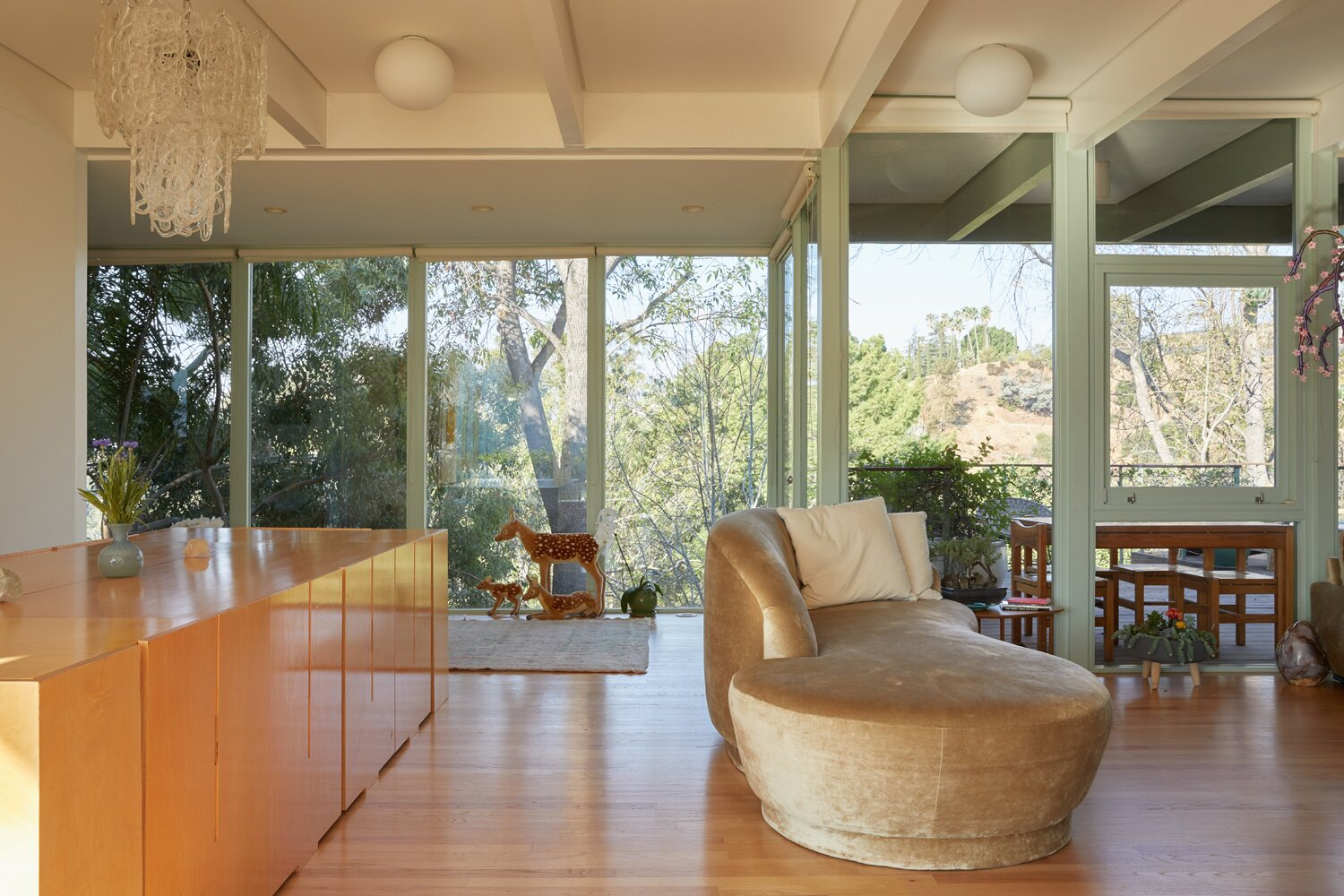 Opposite the sunken sitting area, an open living and dining room offer views of the surrounding treetops.  Photo 3 of 17 in A Hilltop Midcentury Under the Hollywood Sign Seeks $3.6M