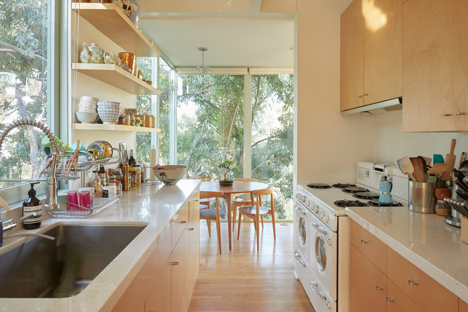 A galley-style kitchen extends from the dining space and connects back to the sunken sitting area at the opposite end.  Photo 6 of 17 in A Hilltop Midcentury Under the Hollywood Sign Seeks $3.6M