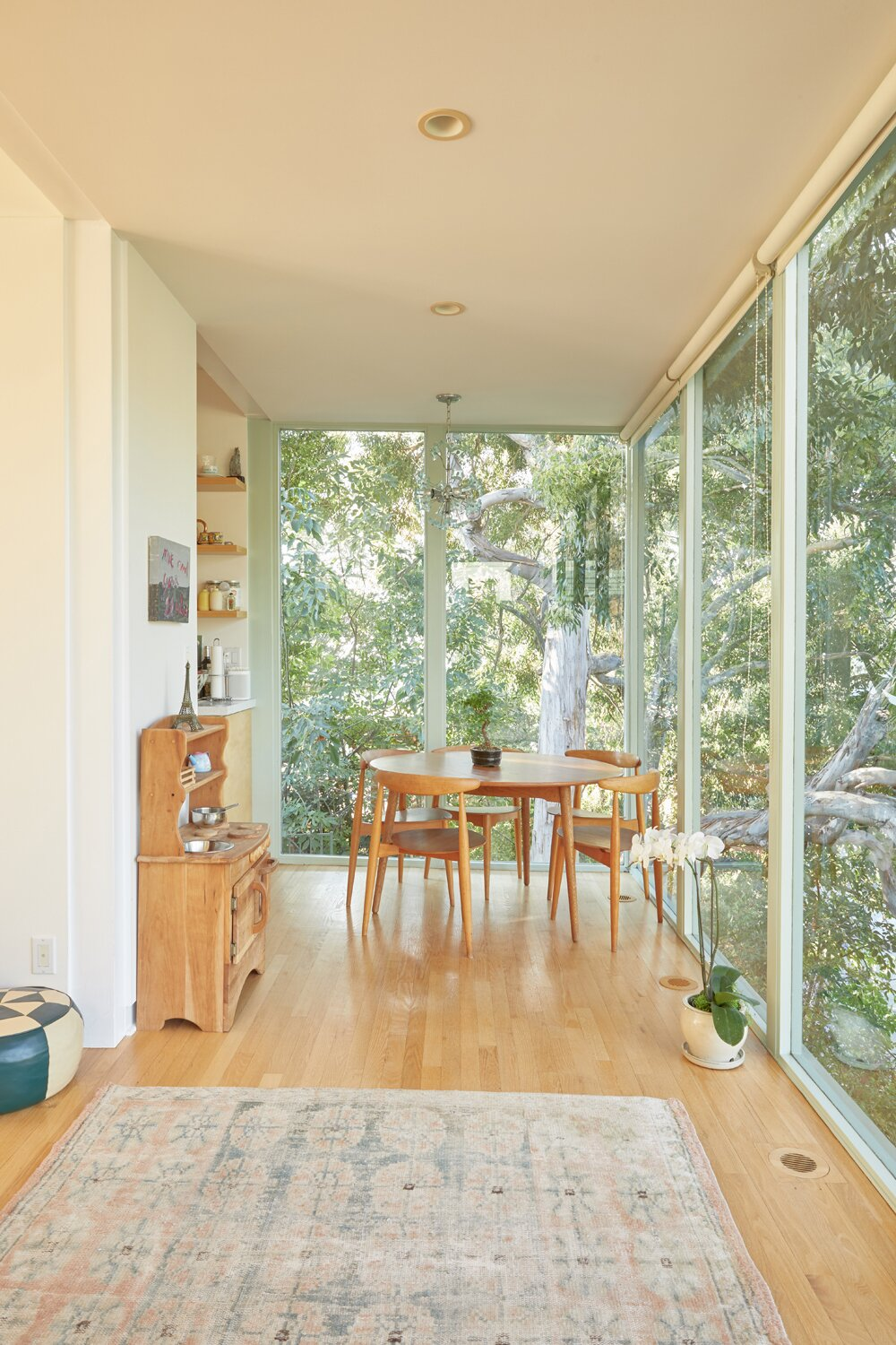 Around the corner, the dining space looks out onto a large tree growing alongside the structure.  Photo 5 of 17 in A Hilltop Midcentury Under the Hollywood Sign Seeks $3.6M
