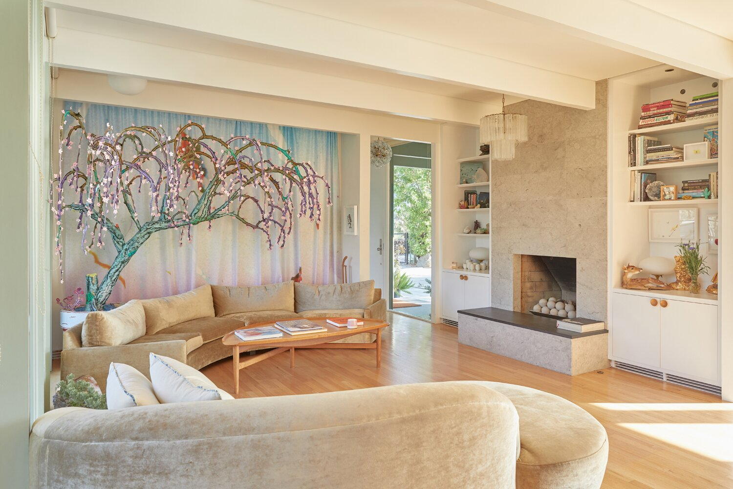 The living room also features a central fireplace flanked by bookshelves.  Photo 4 of 17 in A Hilltop Midcentury Under the Hollywood Sign Seeks $3.6M