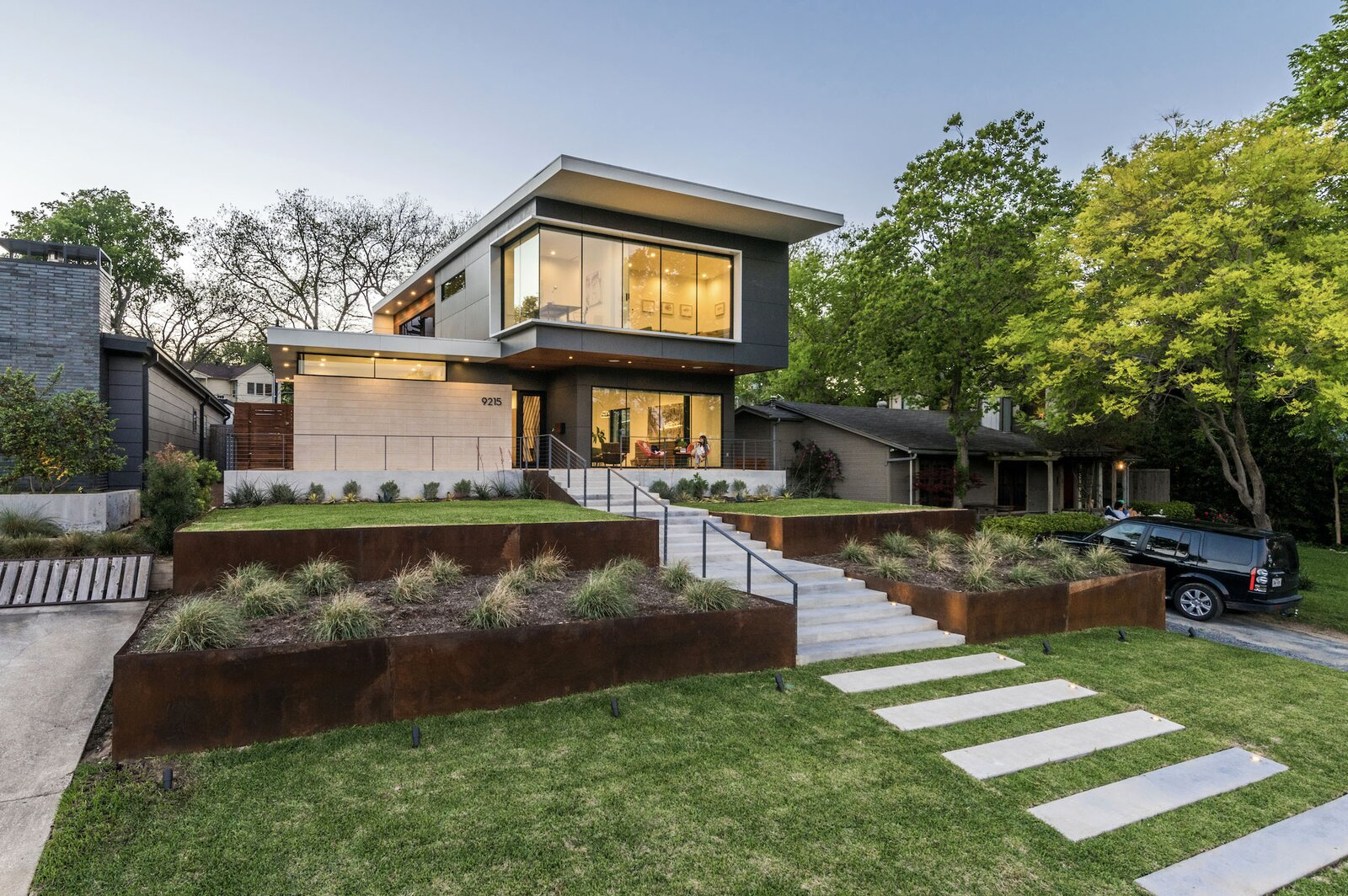 Along the front of the home, tiered landscape sections are bordered by panels of COR-TEN steel, with a central walkway and staircase leading up to the main entrance. The glassy front facade provides multiple vantage points for enjoying views of the active neighborhood.