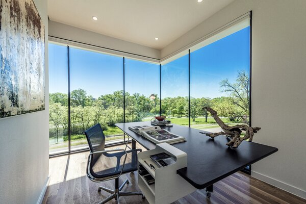 Opposite the second-floor reading area, a home office benefits from the home's most commanding view. Visibility is maximized by a sleek open corner—which uses butt glazed glass that joins each window pane with weather-sealed silicone instead of a bulkier metal frame.