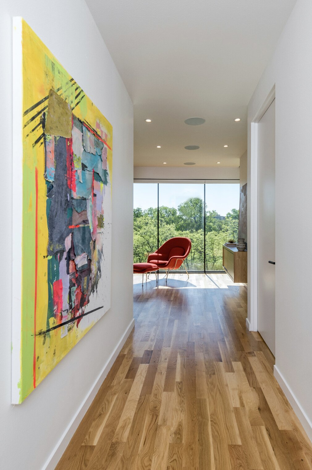 Hallway and Medium Hardwood Floor A central hallway runs through the second story to heighten the experience of entering the reading room and revealing the dramatic glass wall.  Photo 3 of 7 in An Indulgent Fenestration Design Rewards This Modern Dallas Home With Views of a Lush Park