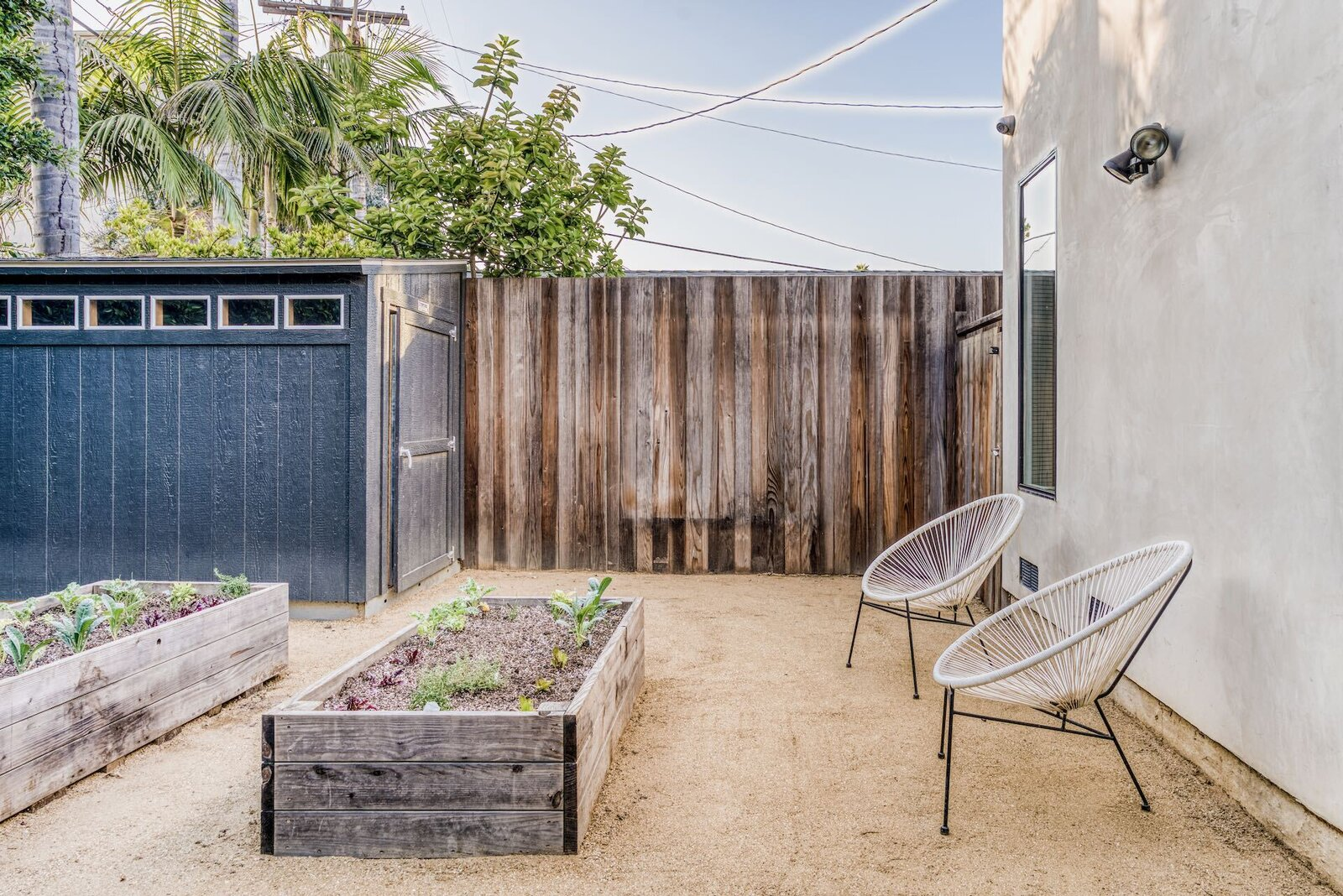 Near the swing set, several raised vegetable beds are located alongside a storage shed.  Photo 9 of 15 in In Los Angeles, a Remixed Craftsman Bungalow Lists for $1.9M