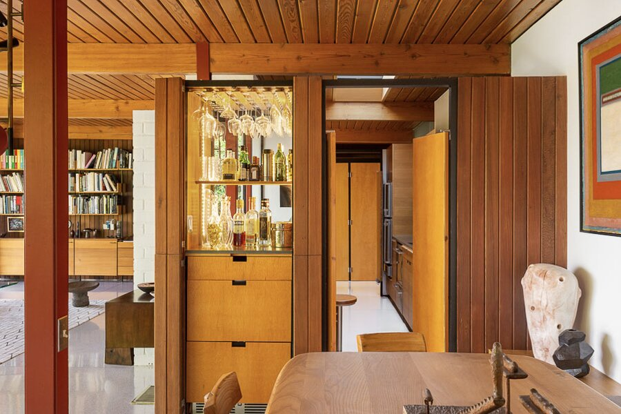 An opposite view of the dining area shows a built-in bar and drawers that were also added during the restoration process. A doorway leads into the kitchen.  Photo 6 of 12 in An Impeccably Renovated Midcentury by Case Study Architect Craig Ellwood Asks $3.75M
